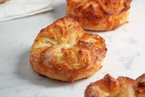 Three koiugn amman--puff pastry coated with sugar--on white marble