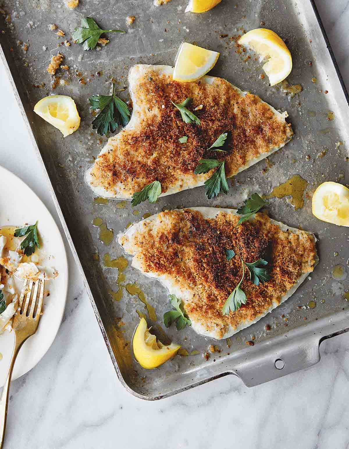Two fillets of lemon sole oreganata topped with a Parmigiano-Reggiano breadcrumb mixture on a baking sheet