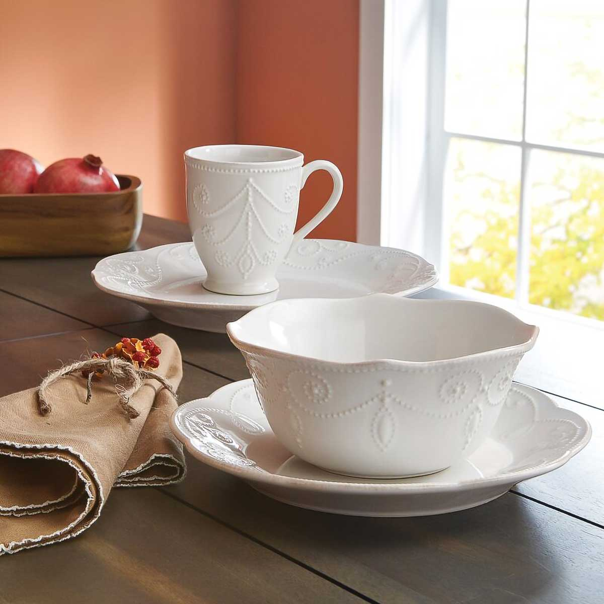 Lenox French Perle Dinnerware on wood table with pomegranates.