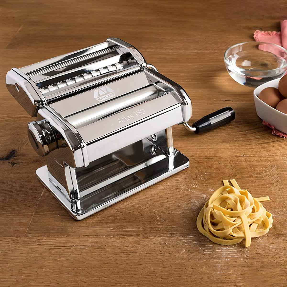 Marcato Atlas 10 Pasta Machine on wood counter with eggs and pasta nest.