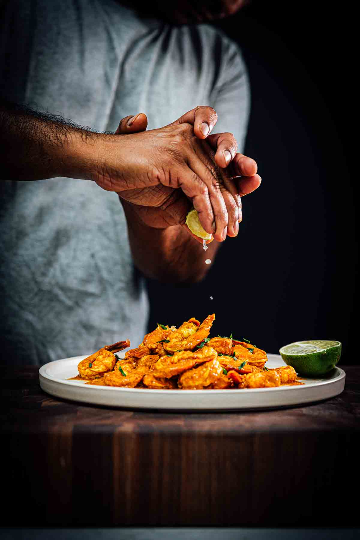 A person squeezing a lime wedge over a plate of masala shrimp.