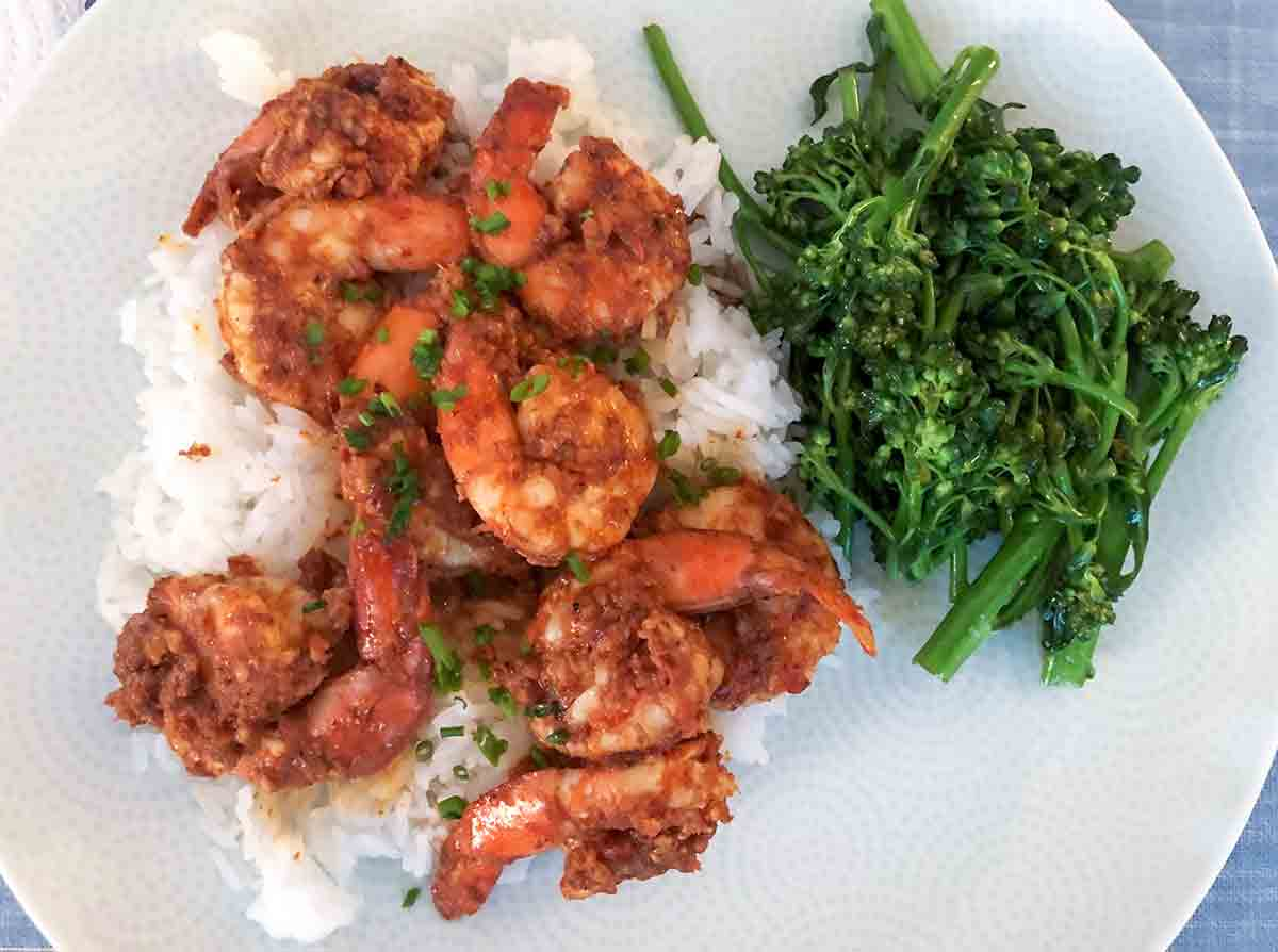 A white plate with masala shrimp, white rice, and steamed broccolini on a blue placemat.