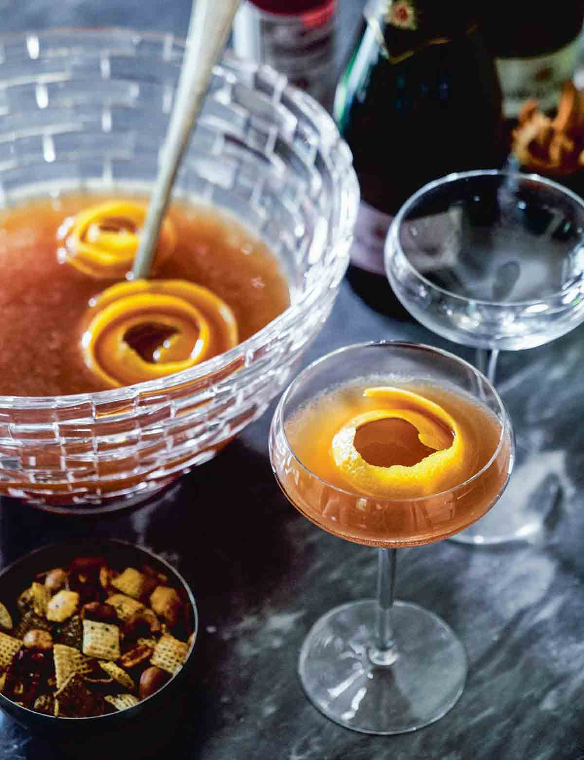A glass punch bowl partially filled with maybelle punch and orange peel garnish, and two coupe glasses alongside, one filled and one empty.