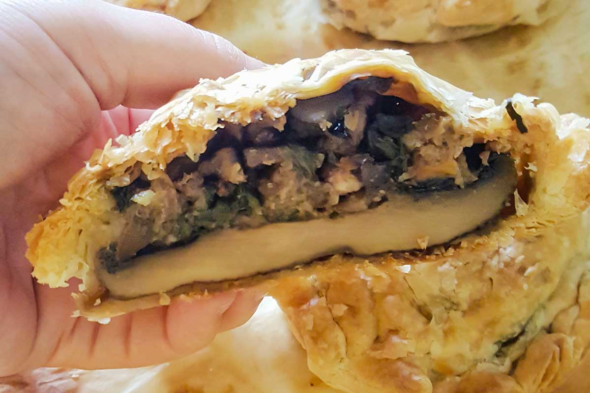 A person holding a halved mushroom wellington with spinach and walnuts.