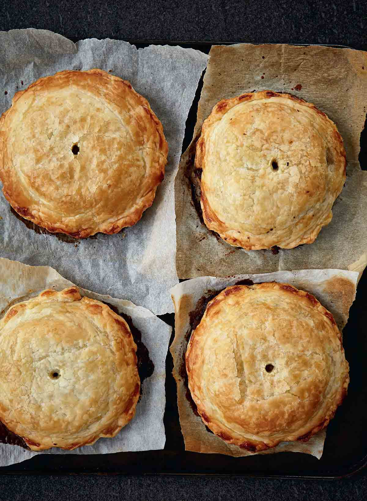 Four individual mushroom wellingtons with spinach and walnuts on a squares of parchment paper.