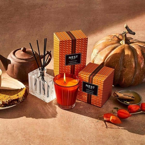 Nest Pumpkin Chai Reed Diffuser shown on brown table with Fall accessories.