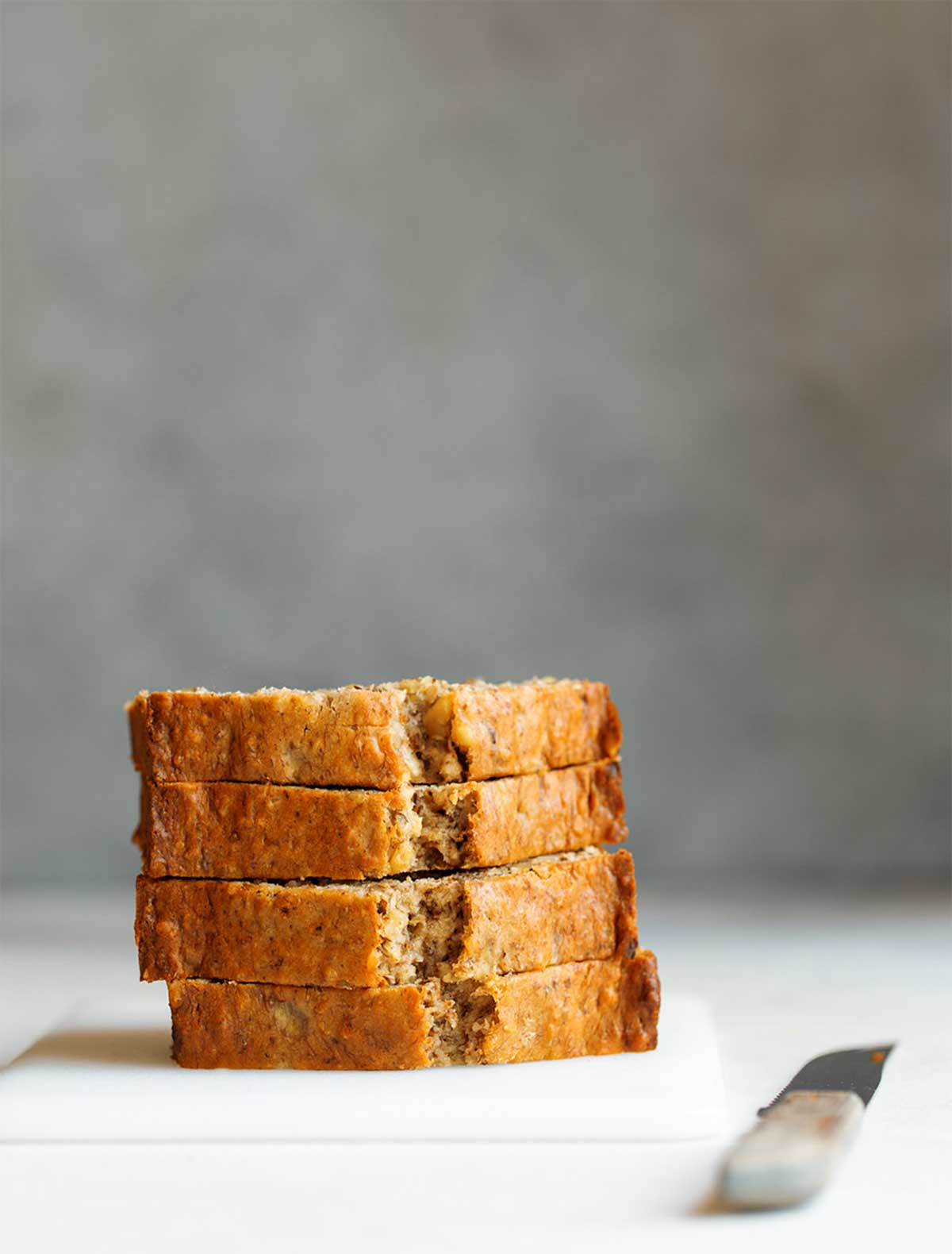 Slices of glazed nutmeg pound cake on a white cutting board