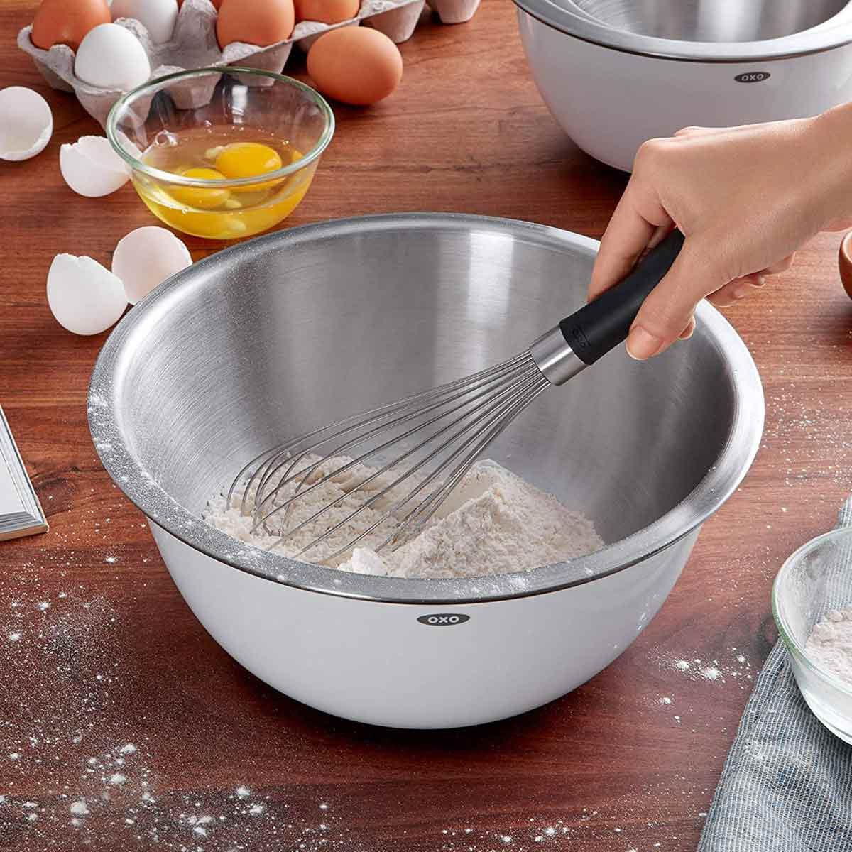 OXO Good Grips Balloon Whisk in use with flour in bowl.