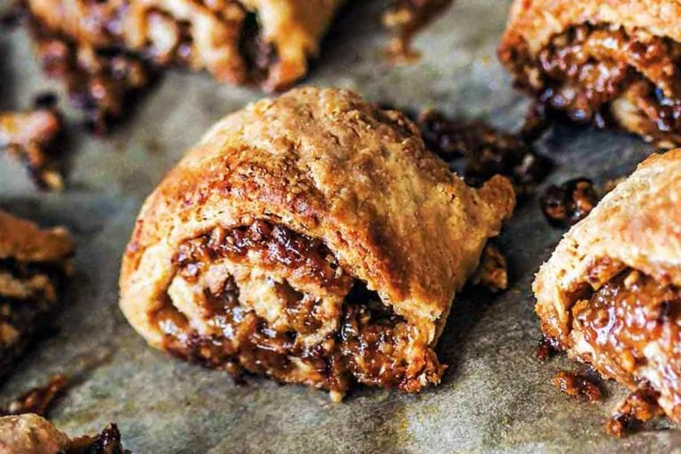 A dozen golden brown pecan pie rugelach with filling oozing out