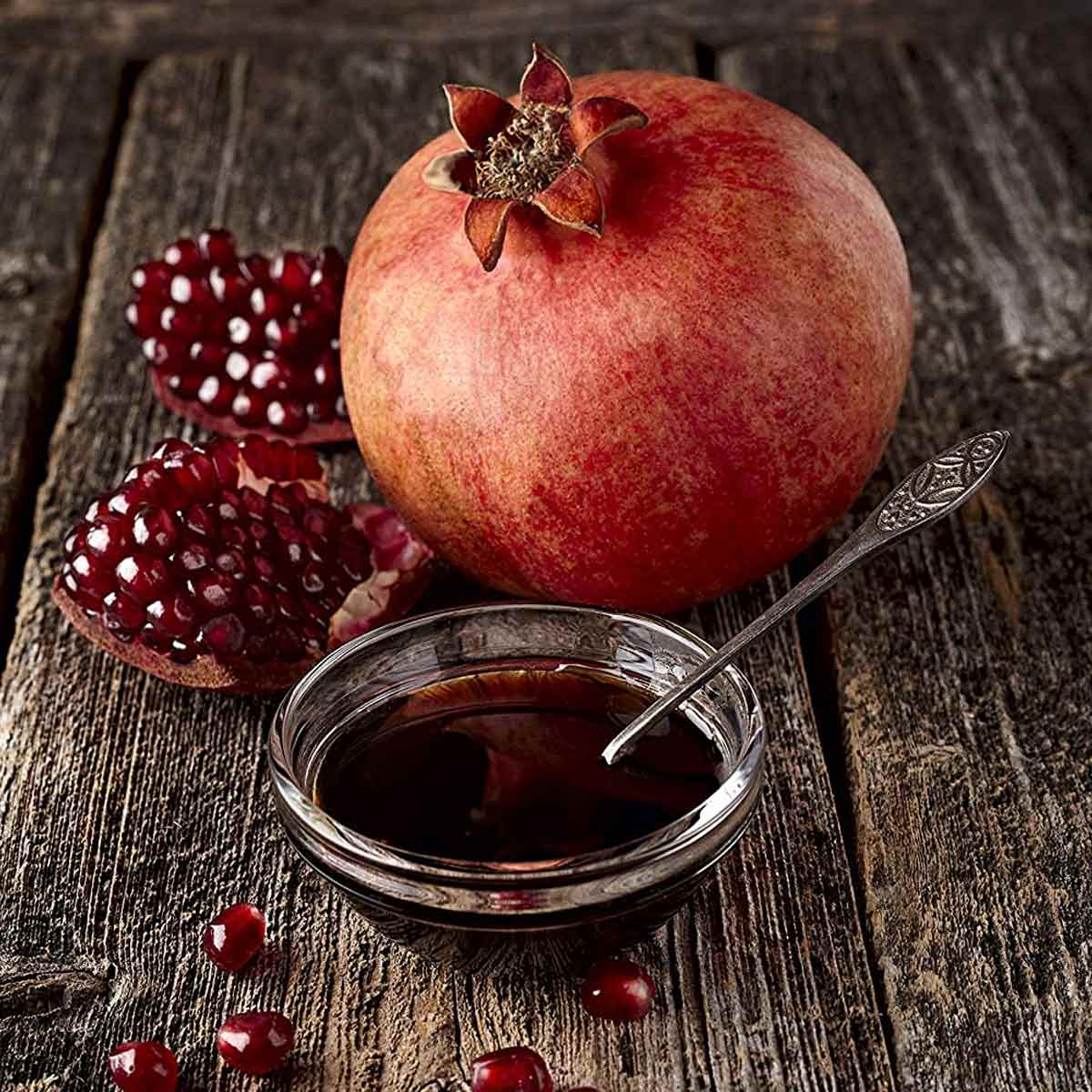 Pomegranate Molasses in clear ramekin with whole pomegranate behind it.