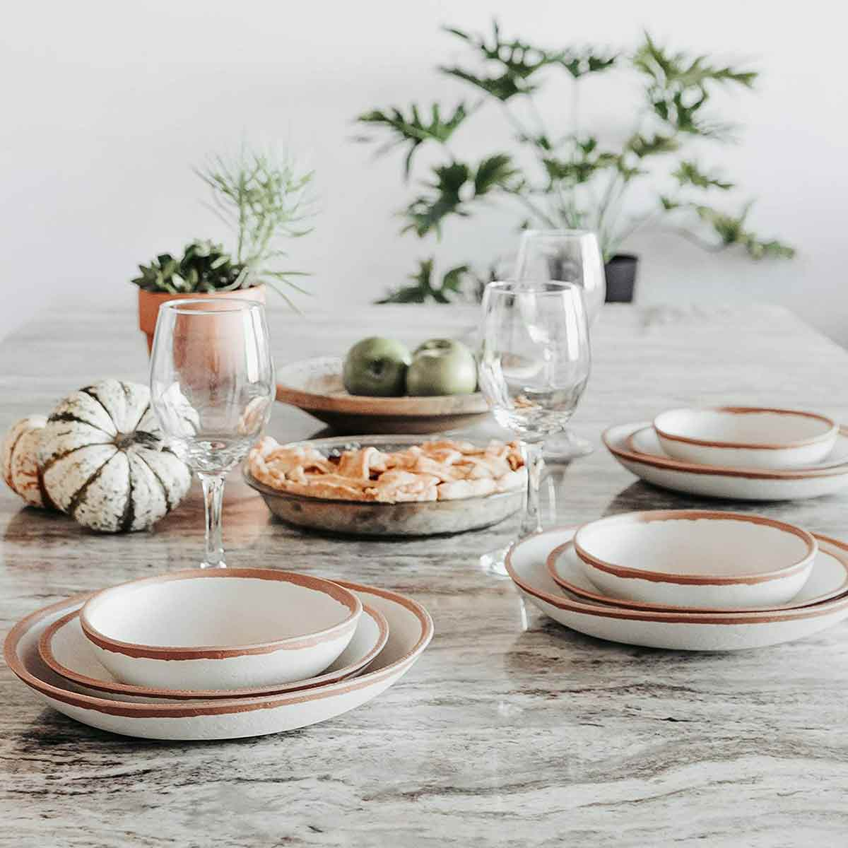 Q Squared Potter Collection Dinner Plate set on table with wine glasses and pie.