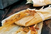 Two wrapped tamales on top of an open corn husk