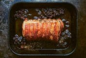 A tied roast pork with crushed grapes in a roasting pan.