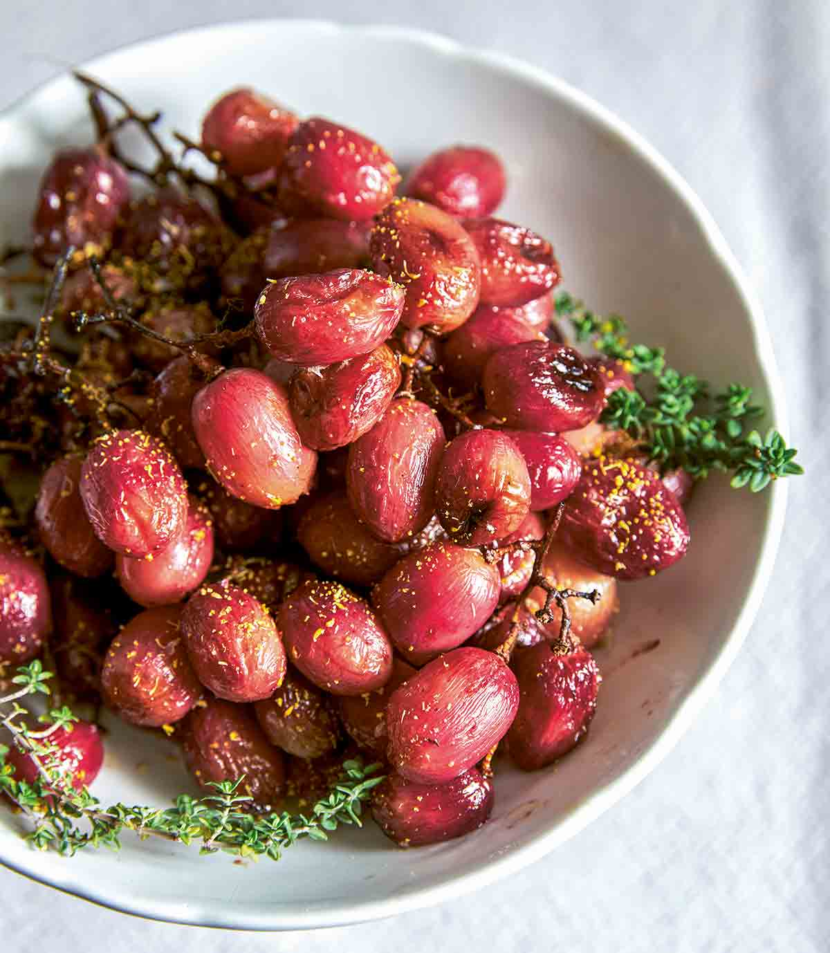 Several bunches of roasted grapes on the vine in a white bowl.