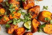 Chunks of roasted sweet potatoes with Sriracha and lime wedges and sprigs of cilantro scattered over the top.