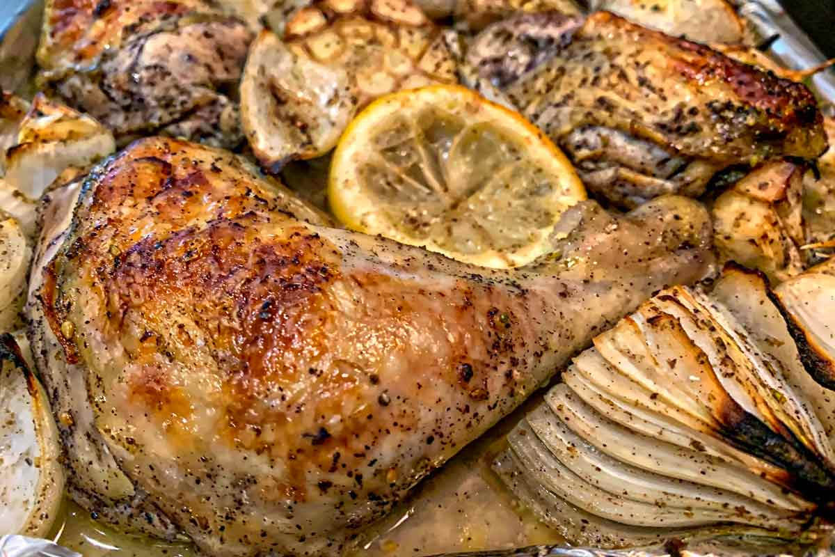 Pieces of sheet pan roast chicken with za'atar with onion wedges, halved garlic heads, and lemon slices.