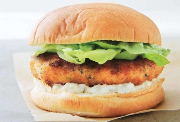 A shrimp burger with tartar sauce, topped with lettuce in a white bun on a piece of parchment paper.