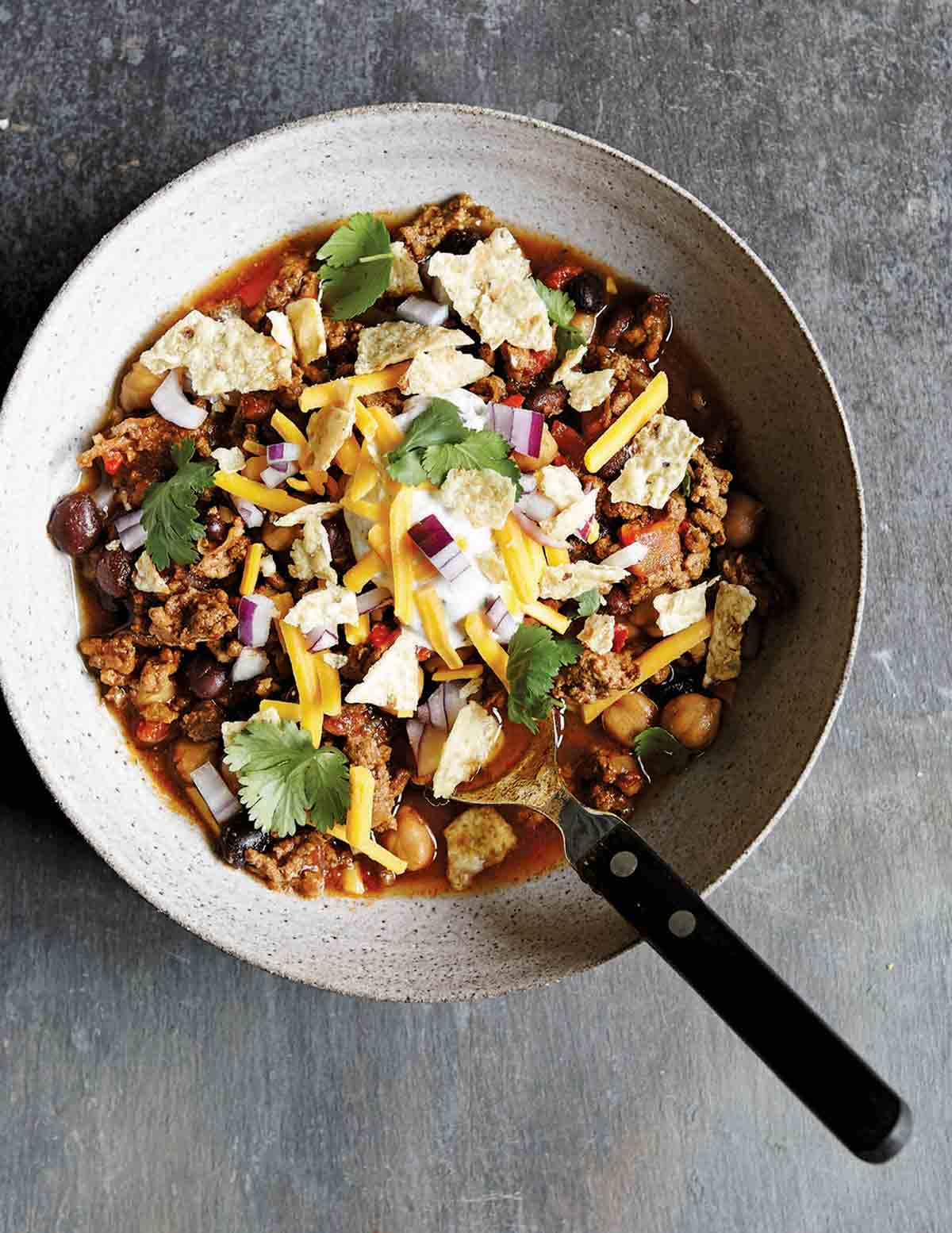 An earthenware bowl filled with slow cooker beef chili, topped with cheese, tortilla chips, and cilantro, with a spoon resting in it.