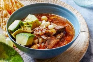 A bowl of pork, avocado, and hominy in a red broth on a cutting board with tortilla chips