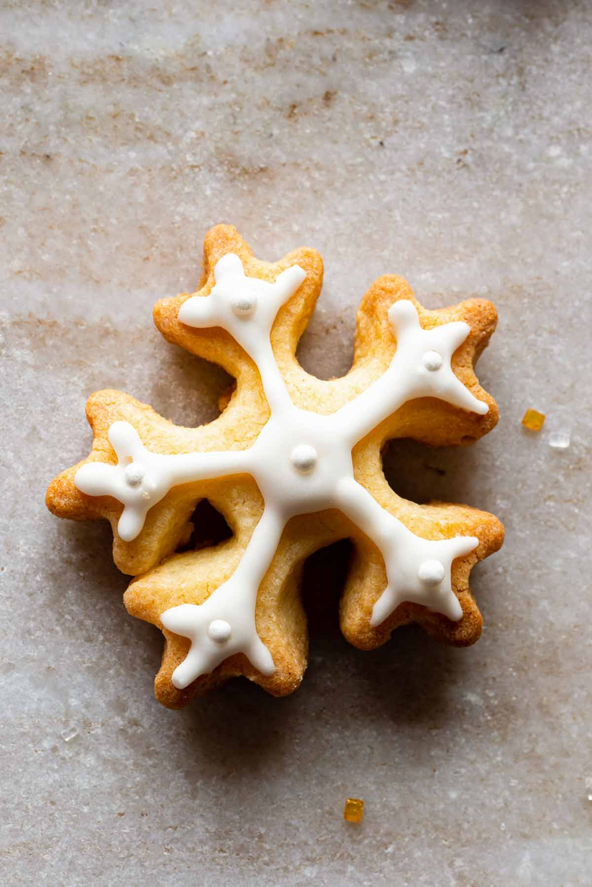 A snowflake cookies frosted with royal icing on a granite background