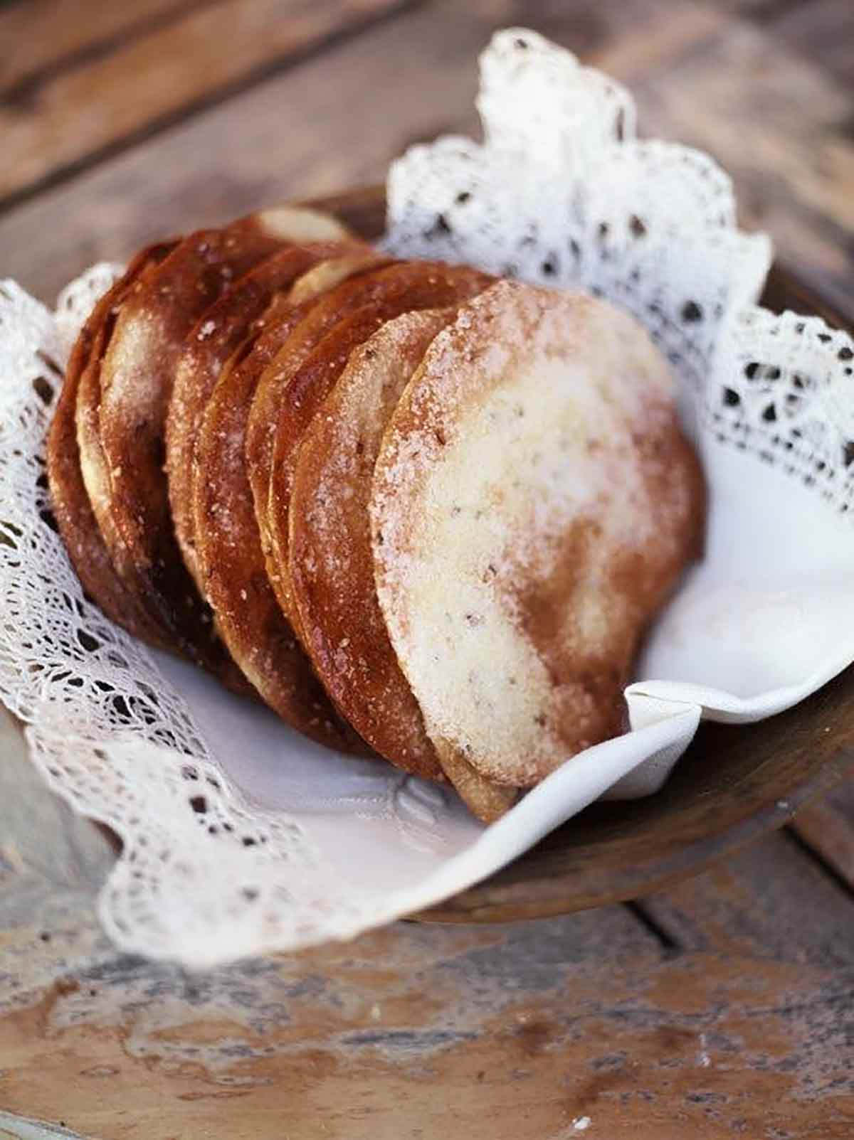 Several Spanish olive oil tortas in a bowl lined with a lace linen cloth.