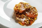 A white plate with three pieces of spicy pepita brittle on it