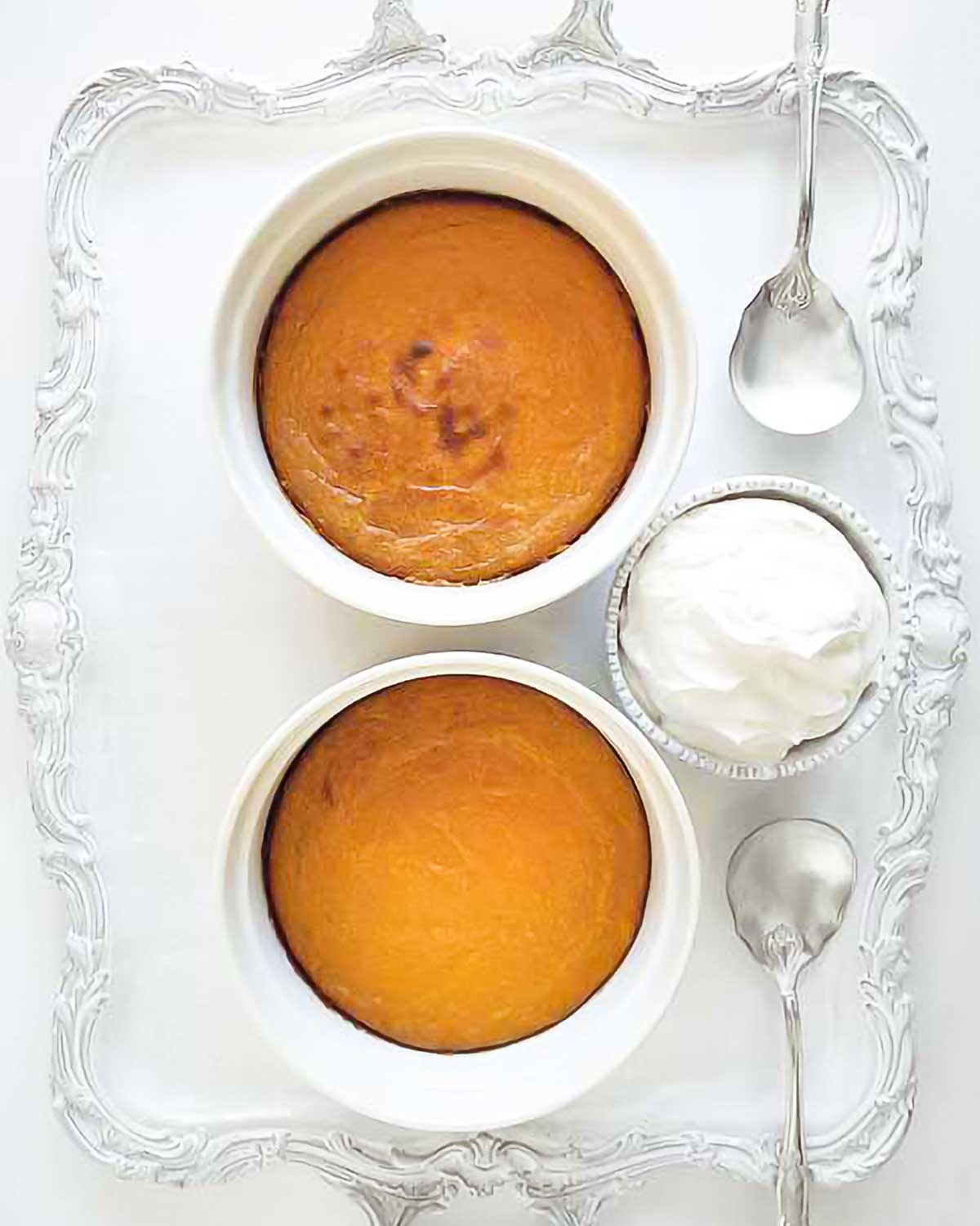 Two sweet potato puddings in white souffle dishes on a silver tray with spoons and a bowl of whipped cream beside them.
