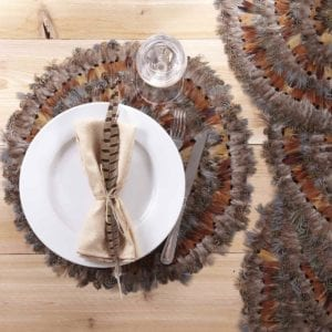 Two's Company Pheasant Placemat, Set of 6 shown with feather in cream napkin.