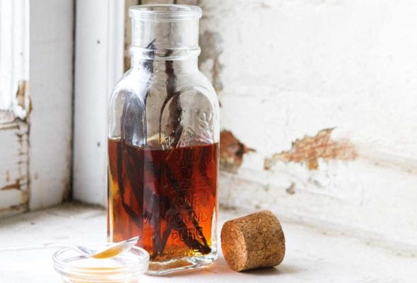 A bottle half-filled with vanilla syrup and a couple vanilla beans inside. A cork rests beside the bottle.