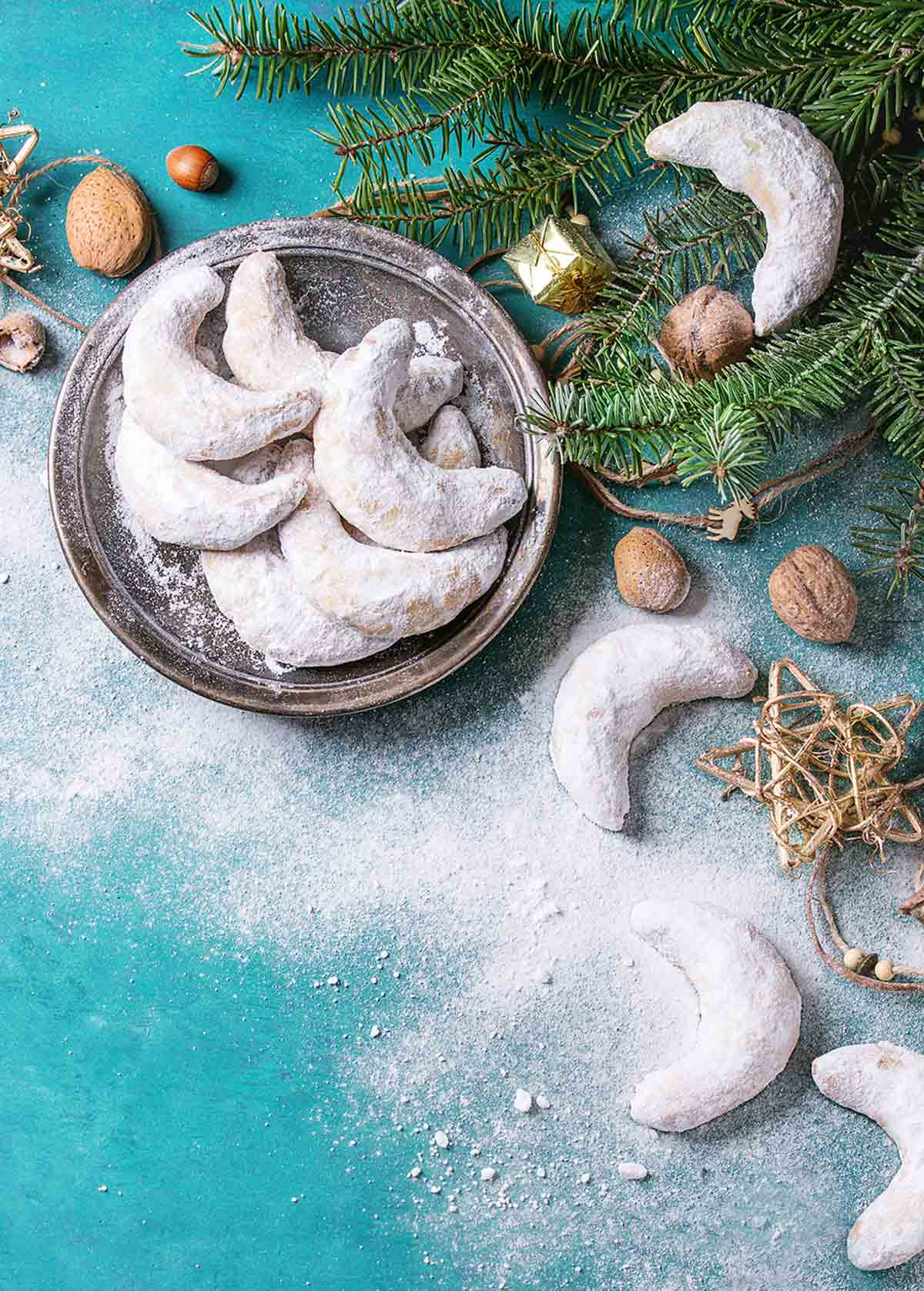 A pile of crescent-shaped cookies on a platter with greenery and Christmas ornaments on the side