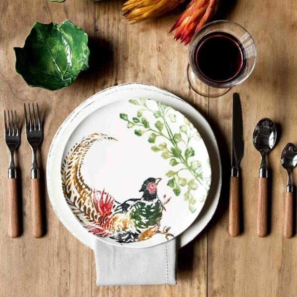 Vietri Fauna Salad Plate on wood table with glass of wine.