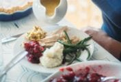 A person holding a gravy boat over a full plate of Thanksgiving dinnner.