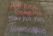 A chalk sidewalk writing that says 'don't kill grandma stay put this Thanksgiving' to illustrate how to have a satisfying Thanksgiving on Zoom (Honest).