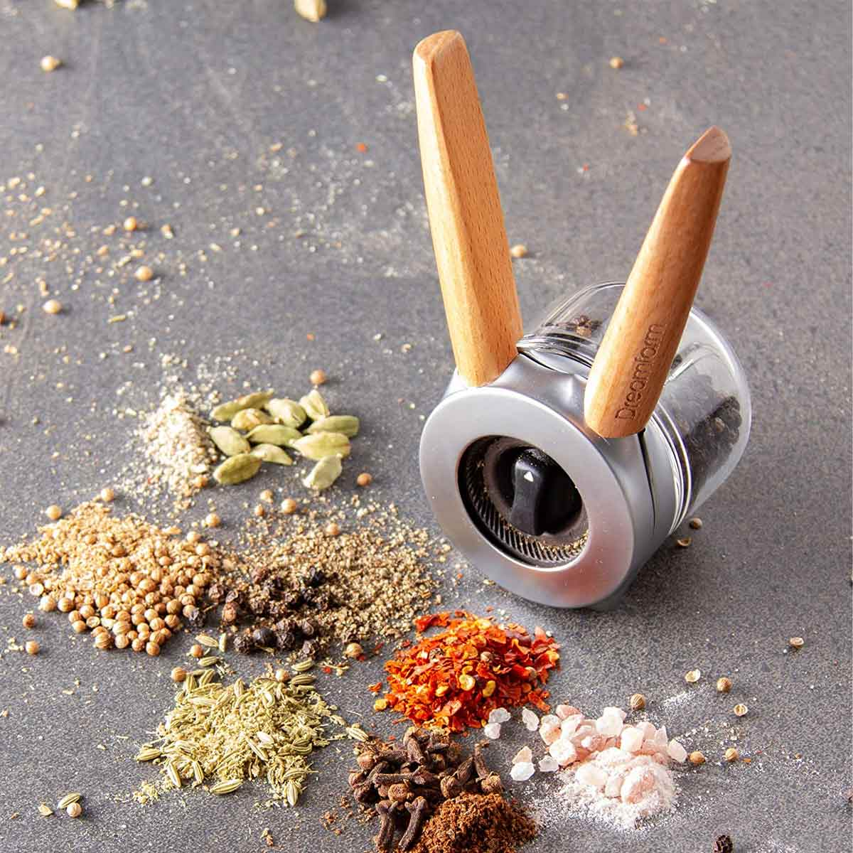 Dream Ortwo Spice Grinder surrounded on table by loose spices.