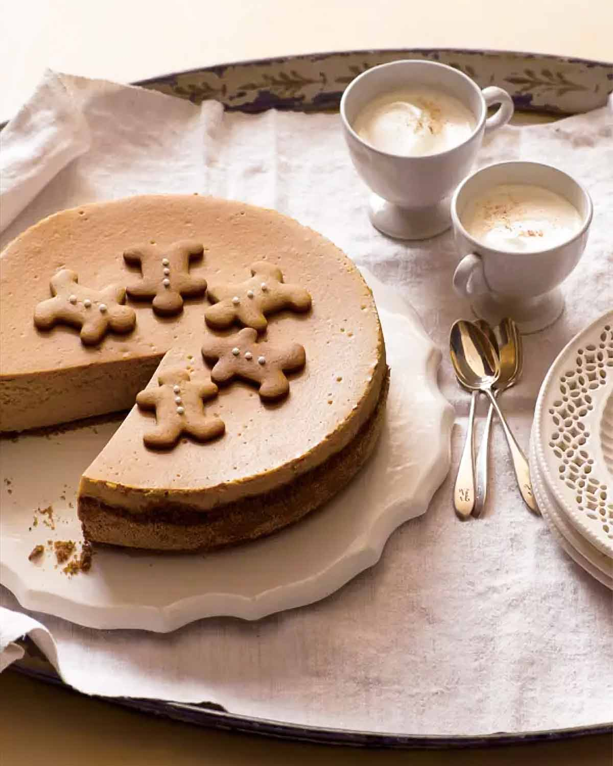 A whole gingerbread cheesecake on a white platter with a slice missing from it.