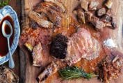Jamie Oliver's Sunday roast carved and displayed on a wooden cutting board.