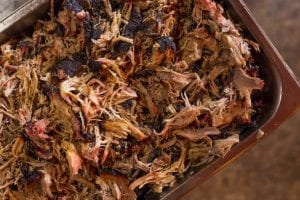 Shredded slow cooker pulled pork in a metal dish.