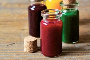 Four bottles of natural food coloring in different shades.