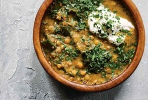 A wooden bowl filled with lentil soup with kale, topped with parsley and sour cream.