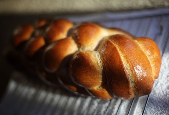A loaf of braided challah on a wire rack.