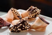 Five change your fortune cookies, coated with chocolate and nuts on a white platter.