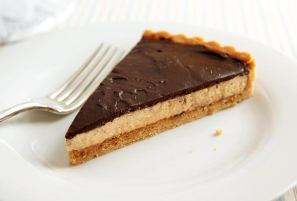 A slice of chocolate peanut butter tart with a cookie crust, peanut butter mousse filing, and a chocolate ganache topping