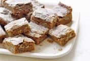 Several cut cinnamon pecan blondies on a white platter.