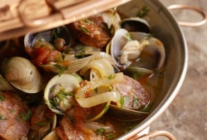 Cooked clams and sausage in a cataplana with onions and tomatoes.