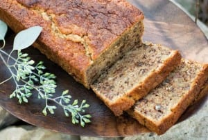 A partially sliced loaf of gluten-free banana bread on a wooden platter.