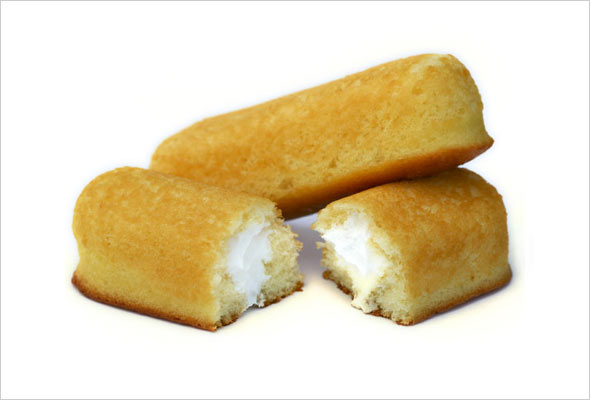 Two homemade Twinkies, one broken in half to show the filling.