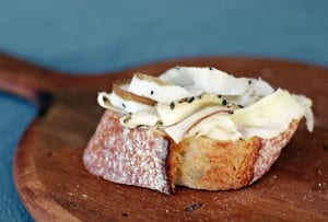 A slice of rustic bread topped with thin slices of lardo, all on a wooden cutting board