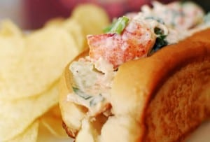 A lobster roll on a toasted split bun, stuffed with lobster in a creamy mayo and lemon dressing with some potato chips on the side.