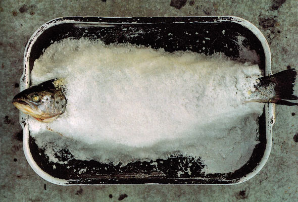 A whole salt-baked wild salmon in a metal baking dish.
