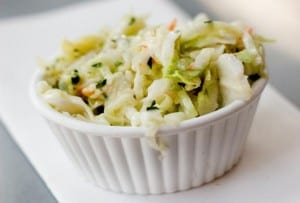 Small white ramekin filled with coleslaw with maple syrup